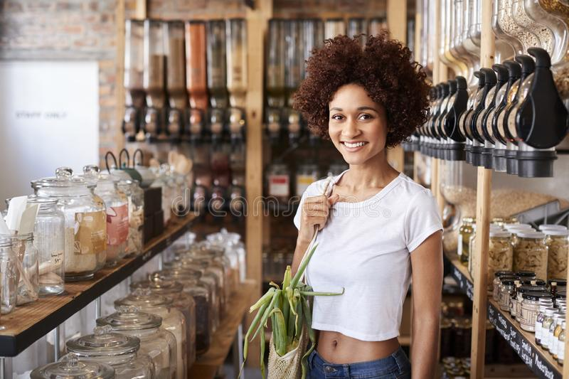Portrait Of Woman Buying Fresh Fruit And Vegetables In Sustainable Plastic Free Grocery Store stock images