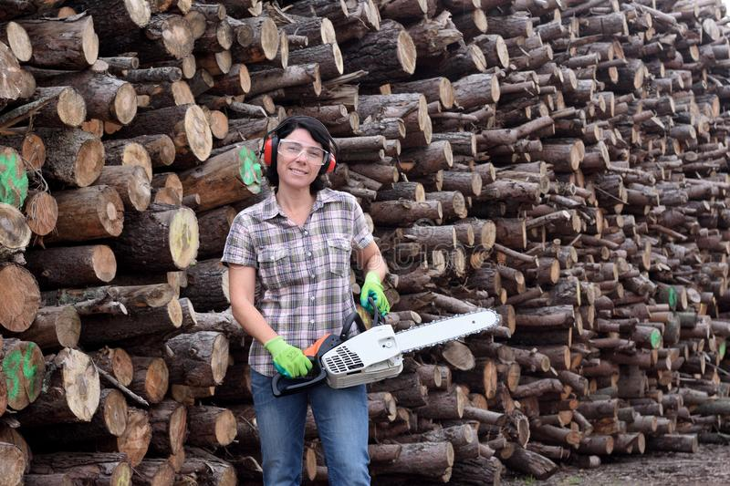 Portrait of a woman with a chainsaw royalty free stock images