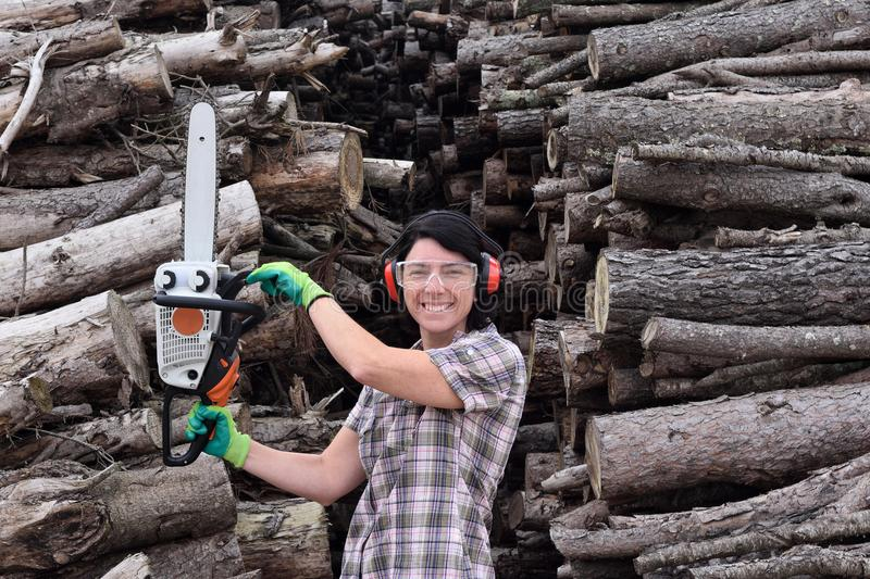 Portrait of a woman with a chainsaw royalty free stock photo