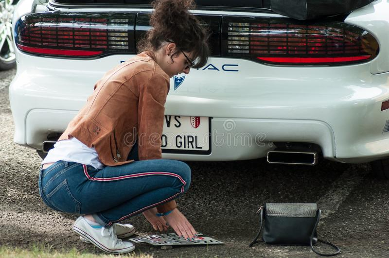 Portrait of woman changing bad girl license plate  vintage american car from Pontiac brand parked at fun car show event royalty free stock image