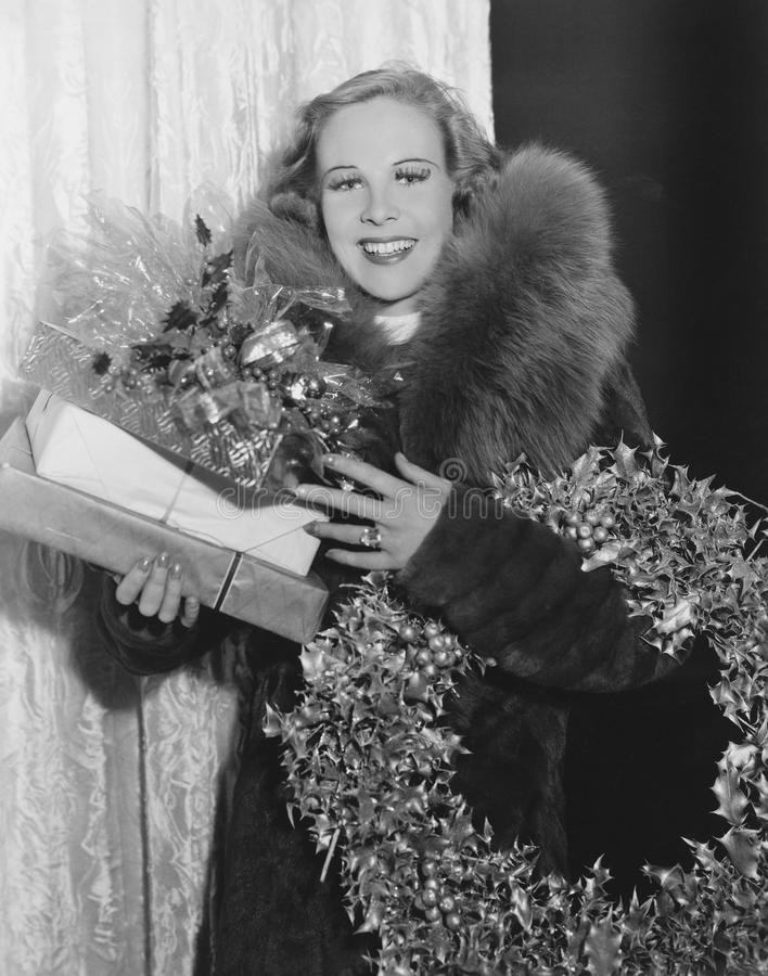 Portrait of woman with Christmas wreath and gifts. (All persons depicted are no longer living and no estate exists. Supplier grants that there will be no model stock photos