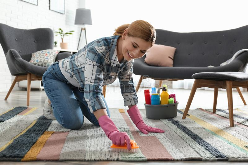 Portrait of woman cleaning carpet with brush stock images