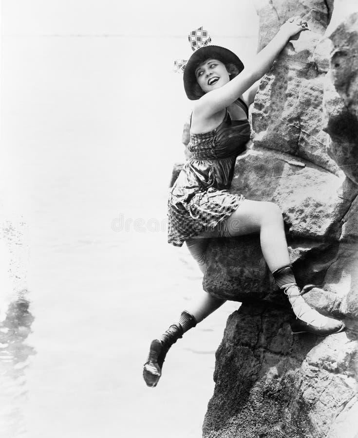 Portrait of woman climbing rock cliff royalty free stock photos