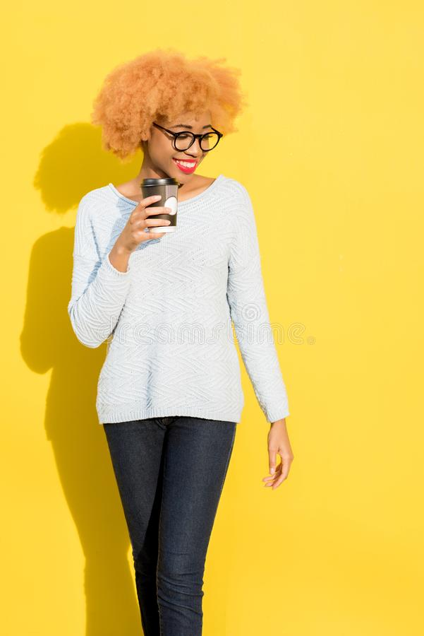 Portrait of a woman with coffee cup on the yellow background royalty free stock photos