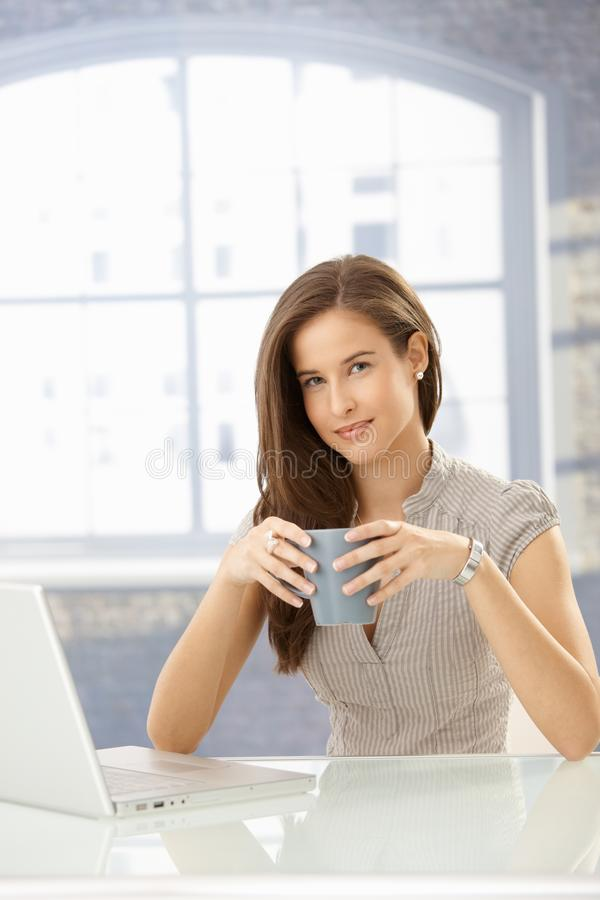 Portrait of woman with coffee using computer royalty free stock image