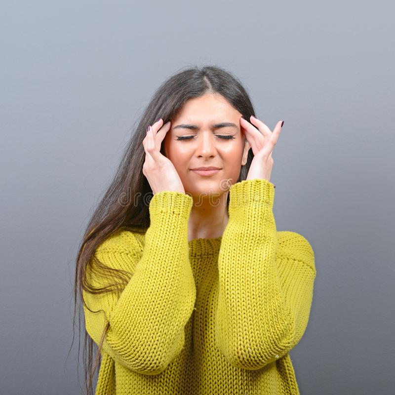 Portrait of woman concentrating against gray background royalty free stock photo