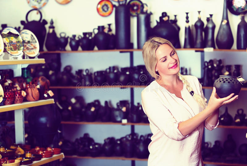 Portrait of woman in craft shop. Portrait of blonde woman in craft shop choosing souvenirs royalty free stock images