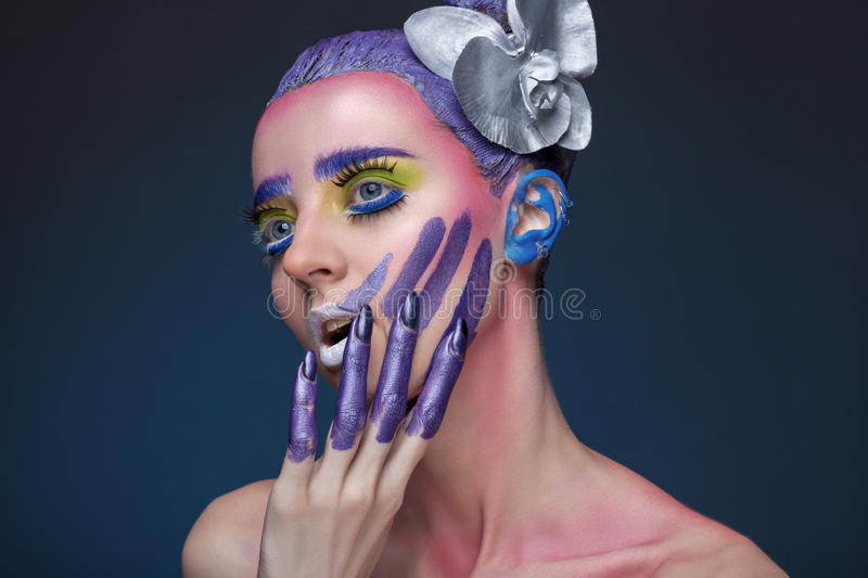 Portrait of a woman with creative make-up. On a blue background. With bright colors on her hair and face. Art beauty. With painted the fingers stock photography