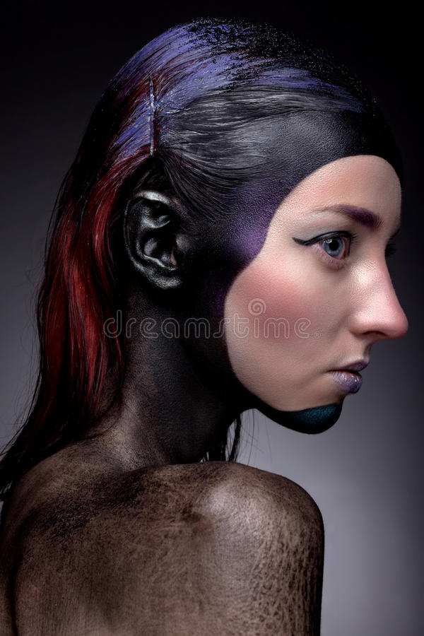 Portrait of a woman with creative make-up on a gray background. royalty free stock image
