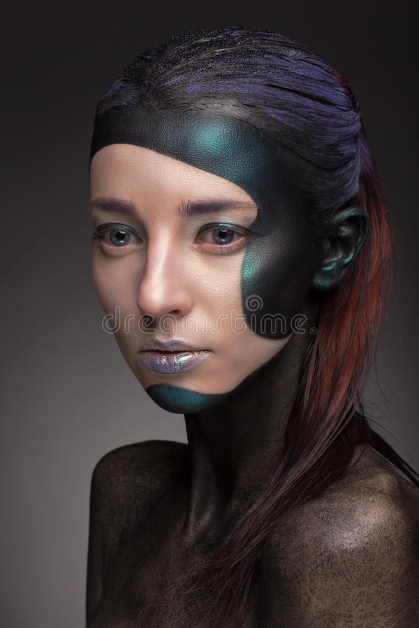 Portrait of a woman with creative make-up on a gray background. royalty free stock images