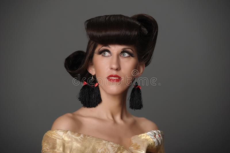 Portrait of a woman with a creative oriental hairdo and long ey stock images