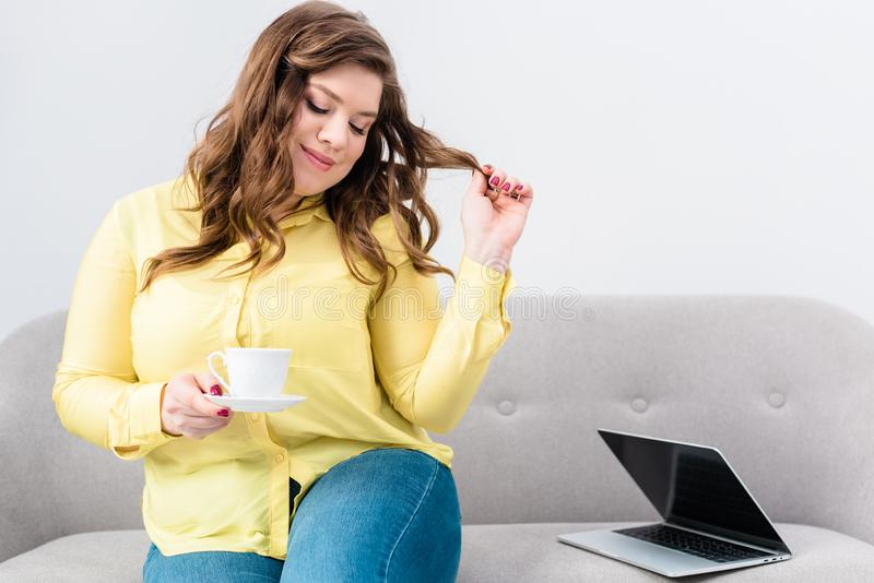 portrait of woman with cup of coffee sitting on sofa with laptop stock photo