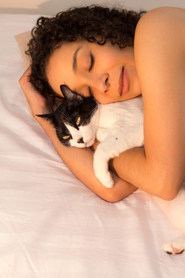 Portrait of woman with curly hair sleeping with her black and white cat in bed. Concept of love to animals, pets, care,. Portrait of mixed race woman with curly royalty free stock photo