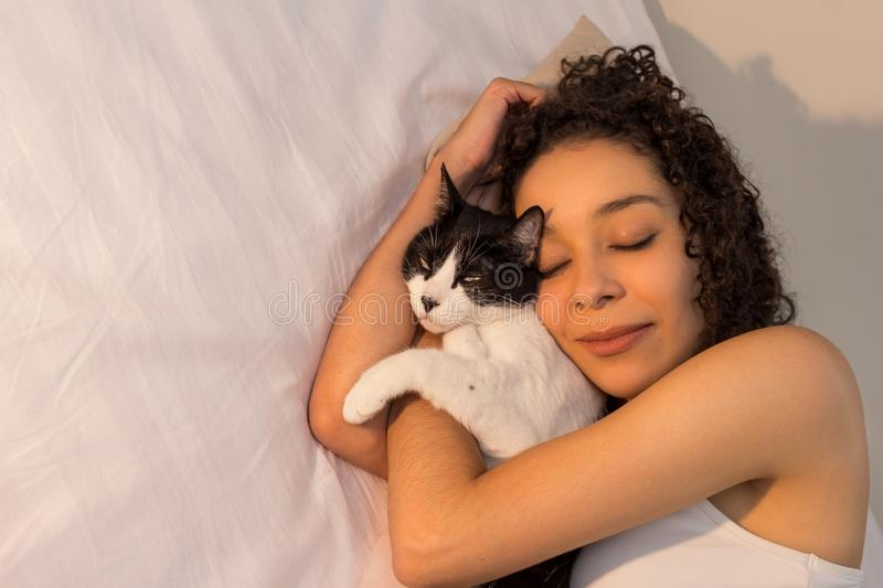 Portrait of woman with curly hair sleeping with her black and white cat in bed. Concept of love to animals, pets, care,. Portrait of mixed race woman with curly stock photography