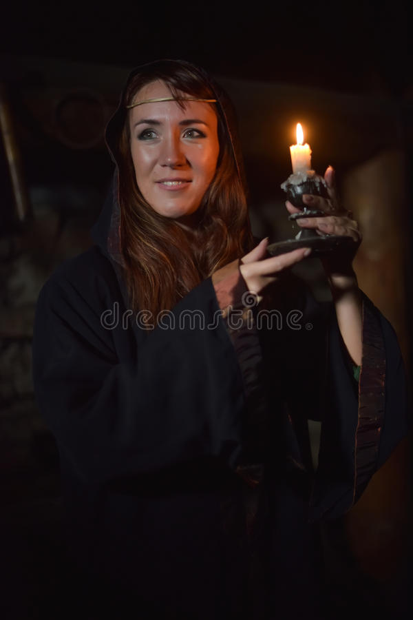 Portrait of a woman in the dark with a candle. In hands stock photography