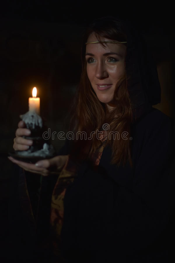 Portrait of a woman in the dark with a candle. In hands royalty free stock images