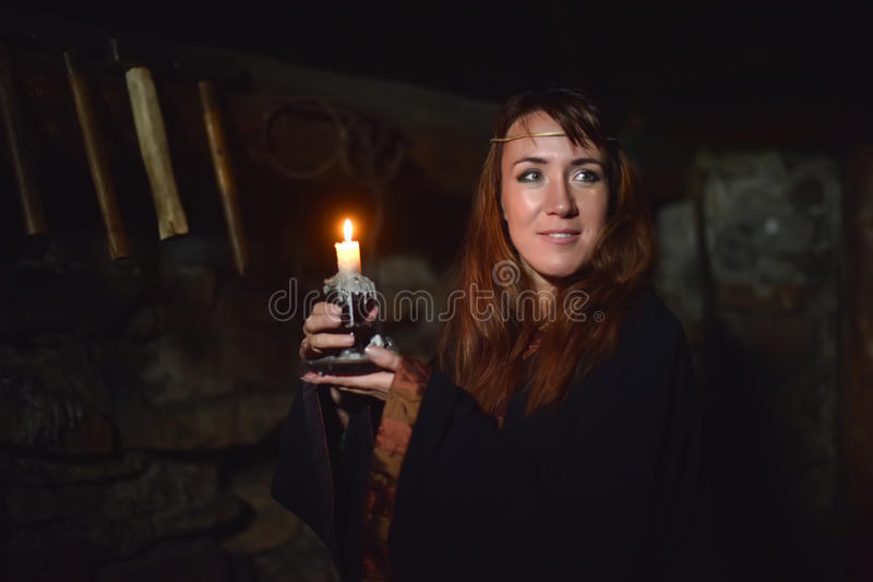 Portrait of a woman in the dark with a candle. In hands royalty free stock photo