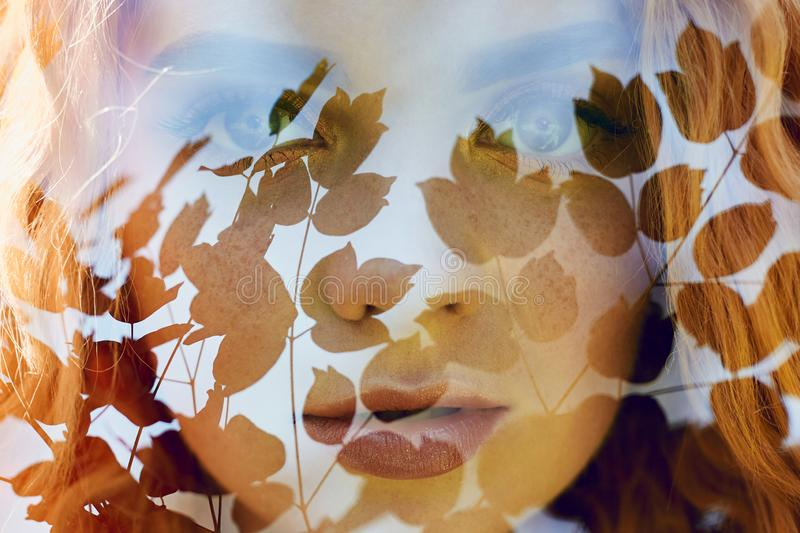 Portrait of a woman with a double exposure, the girl and the blurred nature of the photo is not in focus. The leaves on the woman. stock photos