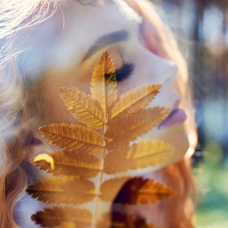 Portrait of a woman with a double exposure, the girl and the blurred nature of the photo is not in focus. The leaves on the woman. stock image