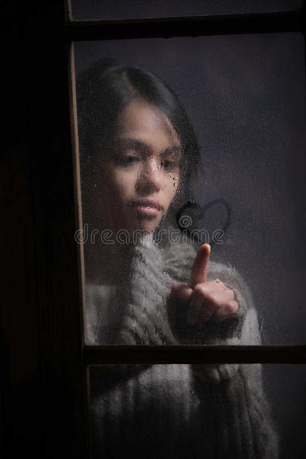 Portrait of woman drawing heart on wet window. Focus on rain drop royalty free stock images