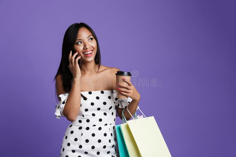 Portrait of woman in dress standing isolated over violet background, holding coffee cup, talking on mobile phone royalty free stock photos