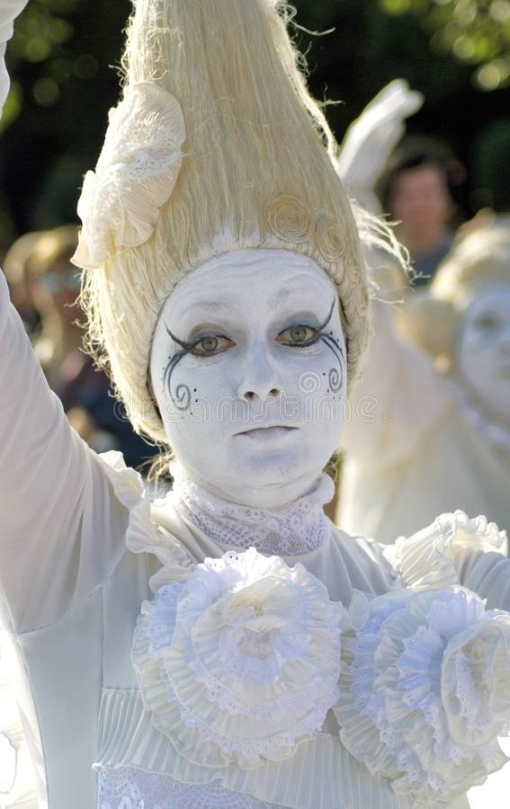 Portrait of a woman dressed in all white, her face is painted in white as well. royalty free stock photos