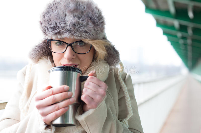 Portrait of woman drinking coffee from insulated drink container during winter royalty free stock photography
