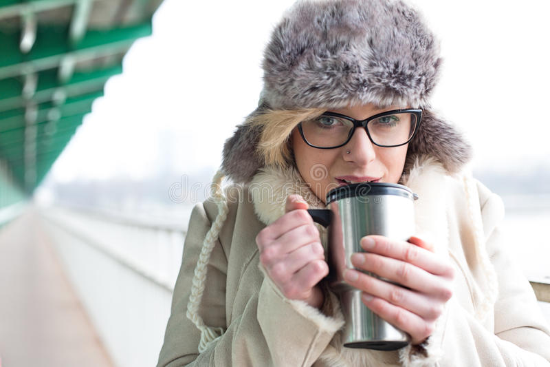 Portrait of woman drinking coffee from insulated drink container during winter stock image