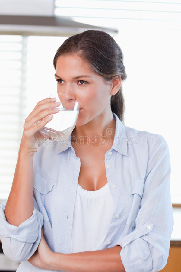 Portrait of a woman drinking a glass of water royalty free stock photo