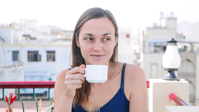 Portrait of woman drinking hot beverage while having a breakfast on terrace. royalty free stock photo