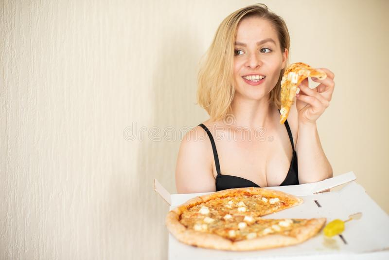 Portrait of a woman eating pizza. Beautiful young woman in black underwear eating pizza stock image