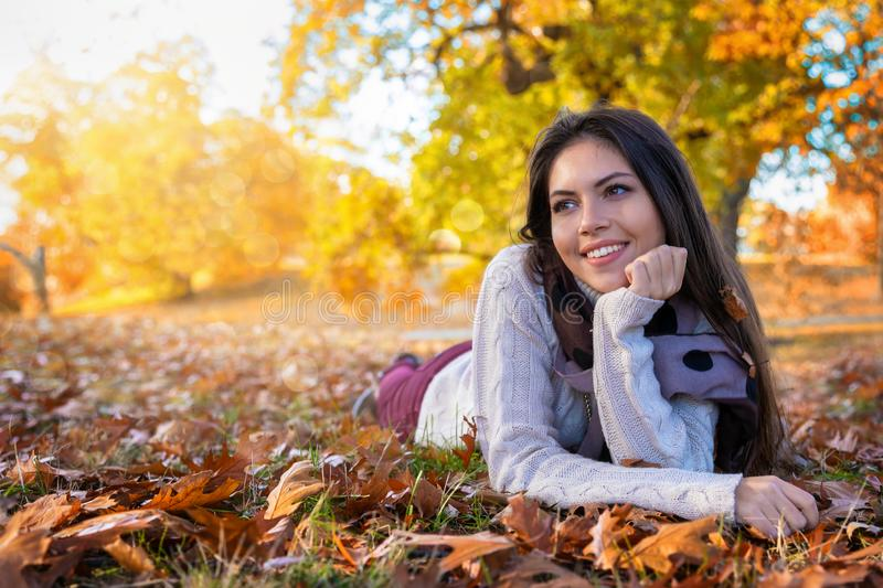 Portrait of a woman enjoying the golden autumn colors in a park. Portrait of an young, attractive woman enjoying the golden autumn colors in a park with leaves royalty free stock photo