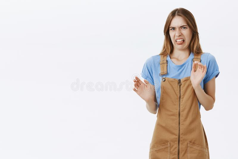 Portrait of woman expressing aversion and dislike sticking out tongue from disgust wanting puke raising palms in refusal. Posing against gray background with stock images