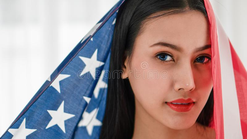 Portrait of woman face with blue eyes with American flag on bright background royalty free stock photos