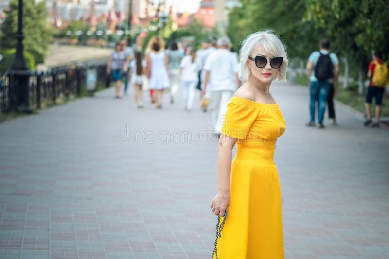 Portrait. fashionable lifestyle. to close. adult blond woman with blond hair in sunglasses walks at street, stylish casual outfit stock photography