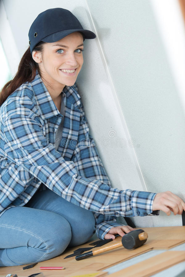 Portrait woman fitting new flooring. Portrait of woman fitting new flooring stock images