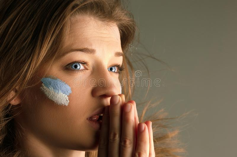 Portrait of a woman with the flag of the Argentina painted on her face. stock photos