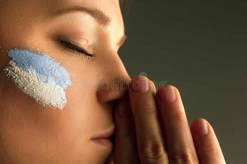 Portrait of a woman with the flag of the Argentina painted on her face. royalty free stock image