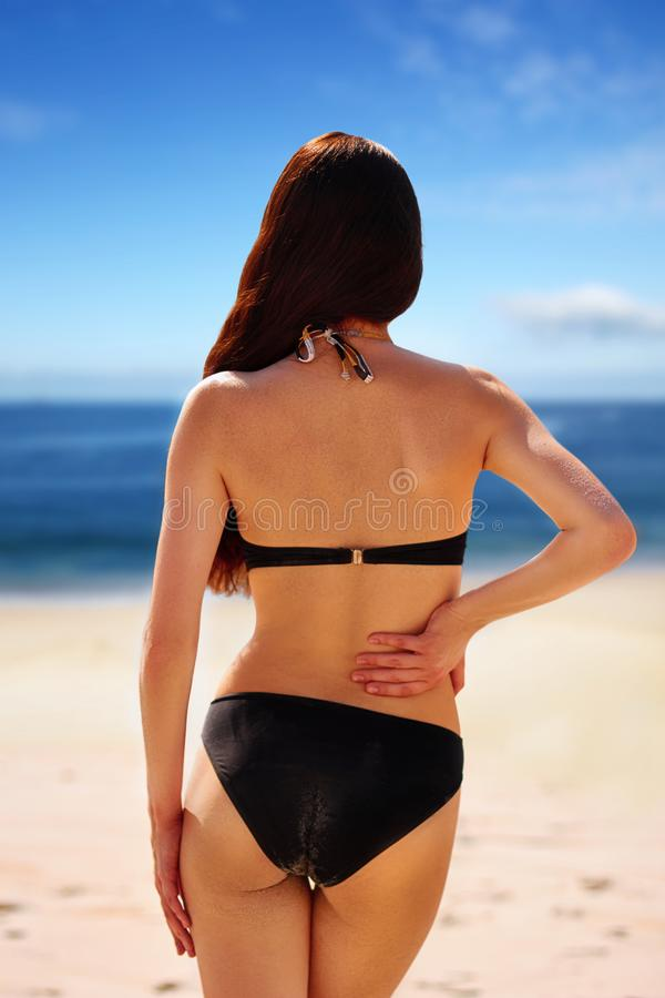 Portrait of woman flaunting her bottom in bikini.Sun Cream. Skin and Body Care. Sunscreen to Her Skin. Portrait Of Female Holding Suntan Lotion and stock photo