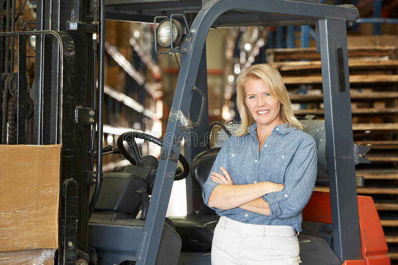 Download Portrait Of Woman With Fork Lift Truck In Warehouse Stock Photo - Image: 29348292