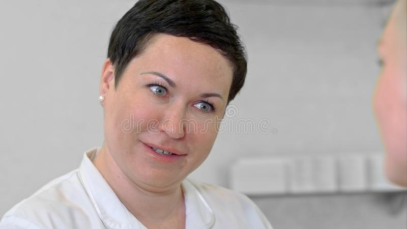Portrait of a woman with fresh and clean skin talking to her client royalty free stock image
