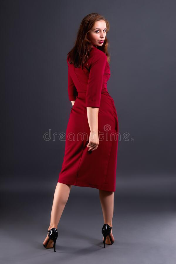Portrait of a woman in full growth, standing with her back and turned to face the viewer royalty free stock images