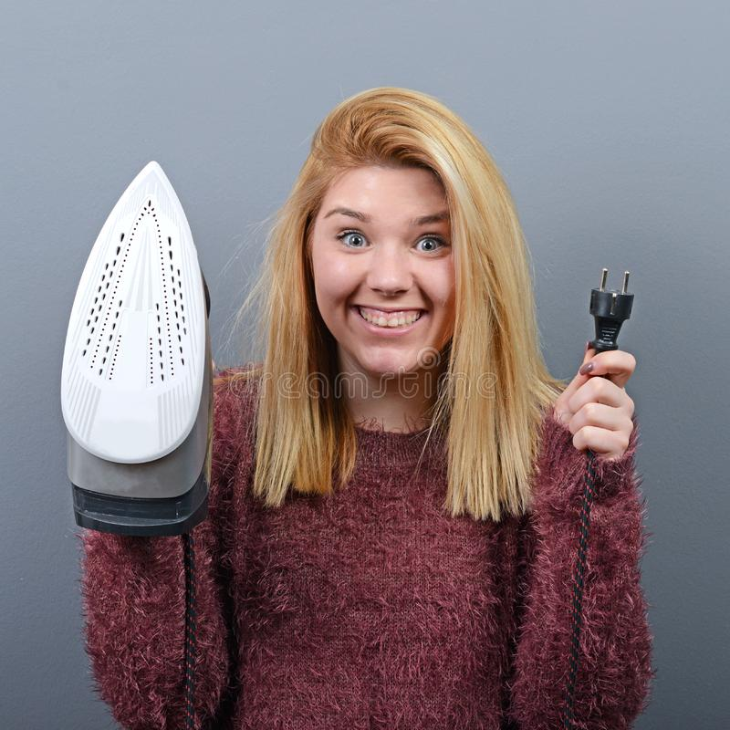 Portrait of woman with funny face holding iron against gray background stock photo
