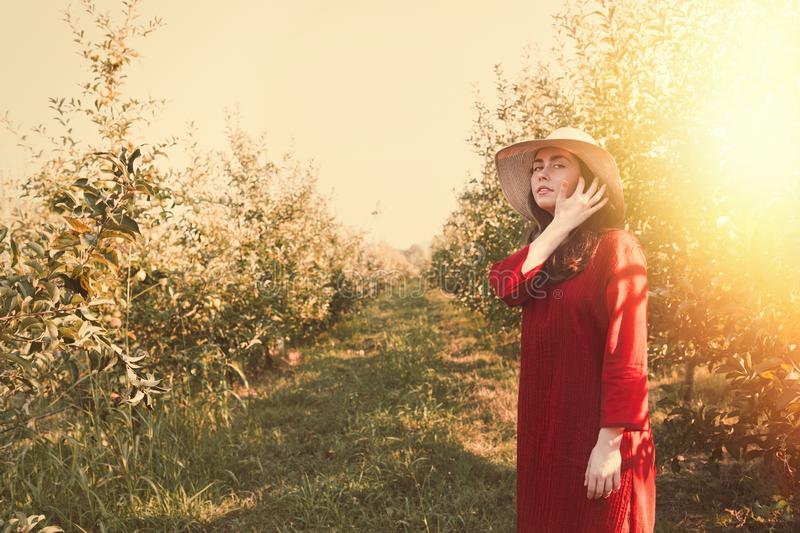Portrait of a woman in the garden. Young and beautiful woman in a red dress and a straw hat, straightens her hair. Hot weather. stock photo