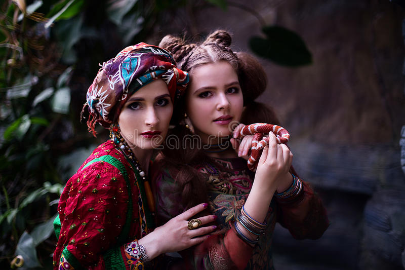 Portrait of woman and girl in ethnic clothes in tropical garden royalty free stock photo