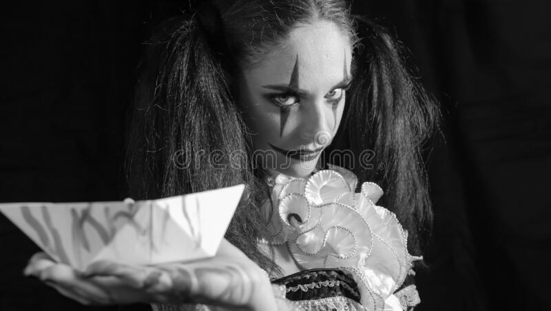 Portrait of a woman. The girl holds a white boat in her open palm. A clown with a smile in a corset. Model with makeup. For Halloween. Girl on black background stock image
