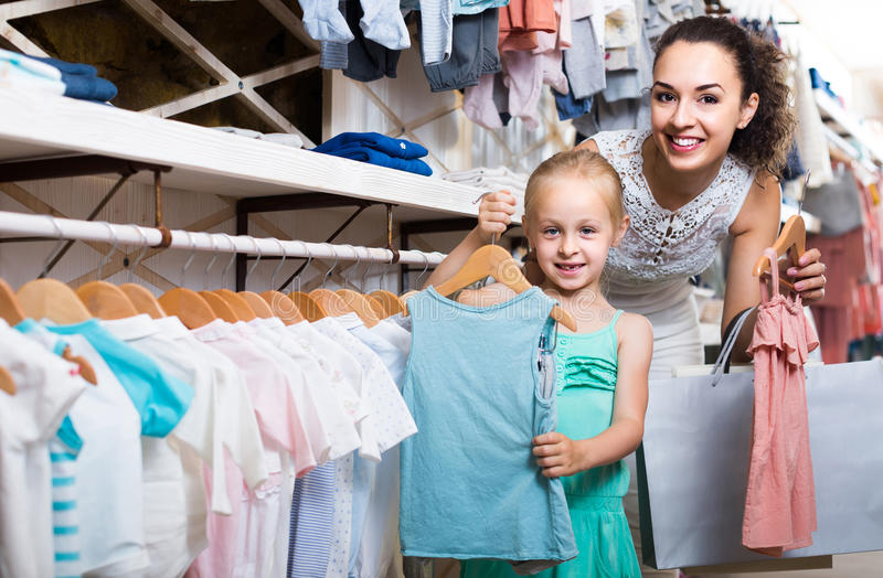 Portrait of woman and girl shopping kids apparel in clothes sto. Portrait of happy spanish women and girl shopping kids apparel in clothes store royalty free stock photography