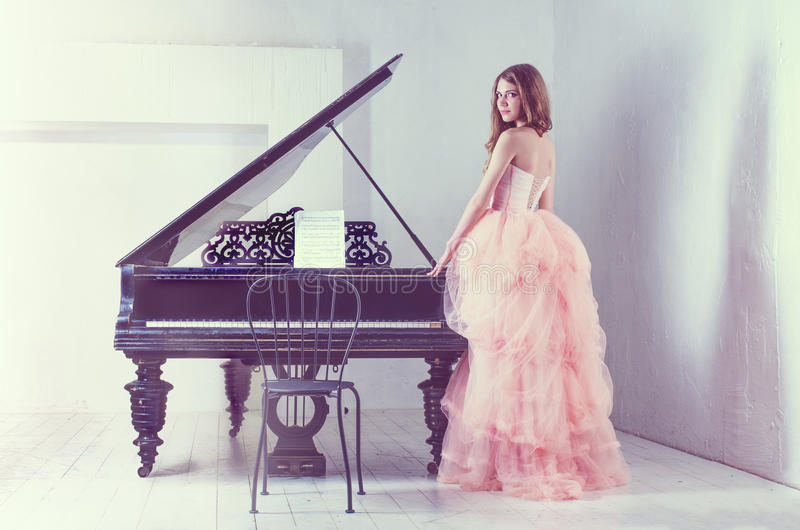 Portrait of woman with grand piano stock images