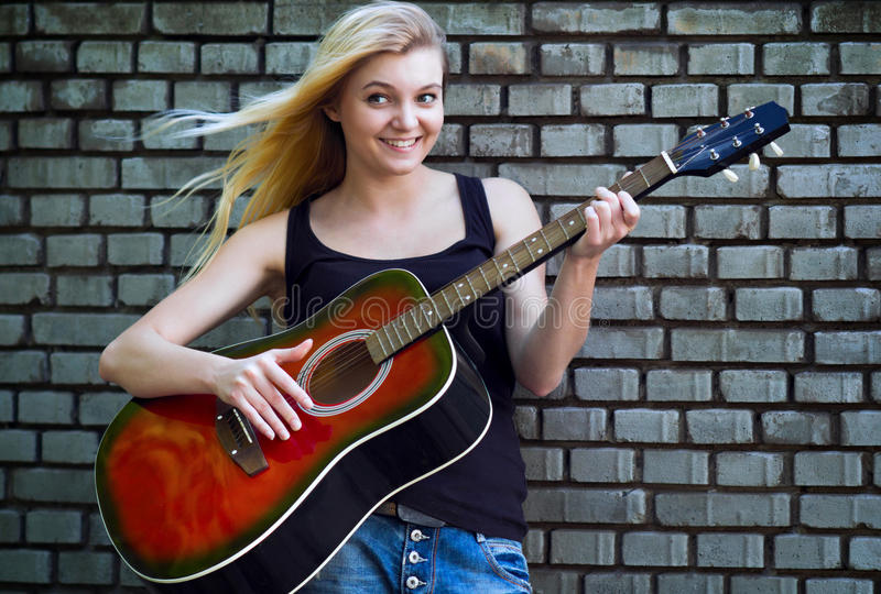 Portrait of a woman with a guitar near brick wall stock image