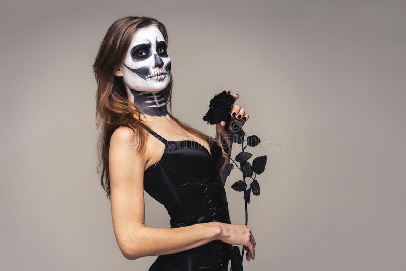 Portrait of woman with halloween skeleton makeup holding black rose flower over gray background royalty free stock photos